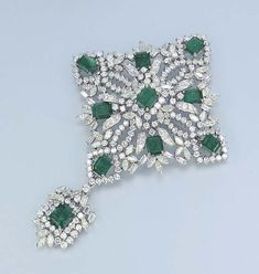 AN EMERALD AND DIAMOND BROOCH    Designed as an openwork lozenge-shaped vari-cut diamond and rectangular-cut emerald panel, suspending a detachable similarly-set pendant, mounted in 14k white gold (with a concealed hoop), 10.0 cm high