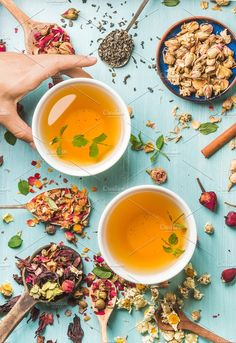 #Two cups of healthy herbal tea  Two cups of healthy herbal tea with mint cinnamon dried rose and camomile flowers in different spoons and woman's hand holding one cup over blue wooden background top view