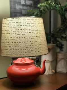 This is a beautiful antique enamel kettle that has been transformed into a lamp. Perfect for any tea lover or for your farmhouse kitchen. The tea kettle is red-orange with a black metal & wood handle. Total lamp height is approximately 13.25 high. Lamp shade base is approximately 10 in
