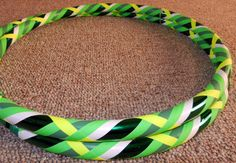 The Tame Taurus Collapsible Hula Hoop is decorated with emerald green mirror deco tape, light green vinyl tape, white vinyl tape, fluorescent green gaffer (grip) tape, and fluorescent yellow gaffer (grip) tape in a crisscross weave pattern. **Fluorescent green & fluorescent yellow gaffer tapes glow in black light!**  https://www.etsy.com/listing/94634746/tame-taurus-collapsible-hula-hoop