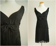 Flirty vintage 1960s black mini dress with a sweetheart neckline, three layers of fringe, and a darling little bow at the bust. Zips up the