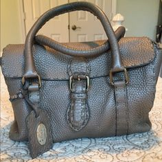 """Fendi handbag 💯% Authentic FENDI sellaria collection. Metallic silver handbag, EUC looks small on the outside but very roomy on the inside. Will fit an iPhone 6s. I'm selling matching wallet too. Stitching intact. Kept in dust bag & is included.  ❌trades, ❌Low ball offers please. Dimensions are: 4d x 9w x 6h opens as wide as 9 1/2"""" deep. Considering all reasonable offers FENDI Bags Mini Bags"""