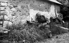 1944, France, Des parachutistes allemands (Fallschirmjäger) au combat armés entre autre de Panzerbüchse Panzerschreck en couverture derrière une maison de pierre