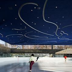 Patterns referencing the footwork of figure skaters decorate the underside of a roof sheltering this ice rink in Brooklyn, New York.
