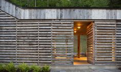 """""""The western, public elevation presents the continuous, wood textured wall that evokes the expressive, scrim wall of a traditional woodshed,"""" write the architects. """"The project purposefully projects a minimal familiar elevation to the non-view, public street side and an engaging, contemporary open elevation to the private hillside."""""""