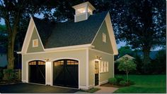 The cutest freestanding garage ever! Love the black barn style doors and the different shades of sage green.