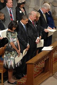 From left to right: the Obamas, and two other couples stand with their heads bowed in a pew