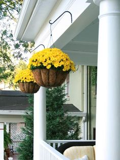 Yellow flowers on a porch....I love those arched holders for the basket that get them far enough out to catch rain showers