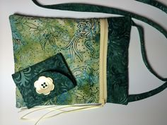 Handmade crossbody bag and wallet of beautiful designer batik fabric and cotton batting. Large open pocket on back and zippered closure with satin ribbon pull on front. 7 x 9 inches with 52 in strap on bag. Wallet is made of same fabrics and has three card pockets as well as a coin pocket with Velcro closure. When closed it measure 4.25 x 3.25 inches and open is 4.25 x 8.5 inches. Tri-folds with Velcro closure.