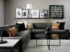 Mooie donker grijze hoekbank met kussens in een honing kleur.