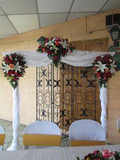 Pergola decorada para boda, con flores y telas.