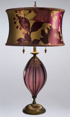 Gabriella Purple Table Lamp  kn-kinzig-design-lighting-gabriella-purple-table-lamp-76k79    This lamp has a smoky silver blown glass base, with a round shade covered in vibrant woven silk in fuschia, grape and salmon. It has two bulbs and a beaded finial and pulls.