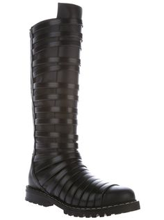 Black leather knee high boots from Gareth Pugh featuring a round toe, contrasting nude stitch detailing, leather straps covering the entire boot, a tall silver-tone zip fastening at the rear and a corrugated rubber sole.