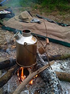 Bedroll camping next to the fire, with a canvas bedroll and kelly kettle.