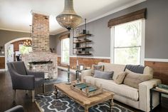 By removing a wall, what was once a small room feels much larger, offering a comfortable flow between the living room and the dining room. In the process of removing the wall, Chip Gaines found the original fireplace and decided to keep it as a unique design element. Original shiplap paneling was revealed and kept as wainscoting around the house, and natural wood cornices were installed around the windows. A large, Art Deco style light fixture illuminates the room, as seen on HGTV's Fixer…