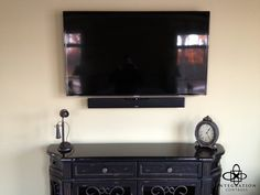 A simple on-wall television installation, paired with a small soundbar, offers better audio that the TV speakers alone. With all wires and 'black boxes' out of sight, the dresser is left clean for simple home decorations.