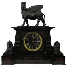 This Art Deco , circa 1920s, mantle clock is a superb example of the Egyptian Revival period. The black marble clock is adorned with bronze sculptures of Egyptian gods. These deities are dramatically positioned atop & at the sides of the body of the clock.  The clock face is accented with stylized Roman numerals viewed through a beveled crystal door.  Unique Egyptian symbols, inlaid in panels of red marble, adorn the lateral aspects of the front of this wonderful timepiece.