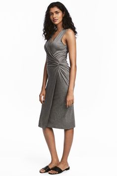 Sleeveless dress in soft viscose jersey with a wrapover front with a decorative knot detail. Seam at the waist and a draped, wrapover, lined skirt.