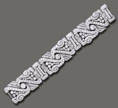 An Art Deco diamond bracelet. The wide flexible band composed of three openwork old European and circular-cut diamond scrolling plaques, enhanced by baguette-cut diamond trim, joined by twin baguette-cut diamond arched links to the pierced pavé-set diamond spacers, mounted in platinum, circa 1930, 7½ ins.