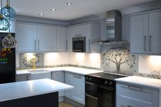 This stunning bespoke fused glass splashback found a home in Condorrat, North Lanarkshire, making the big journey from our Anglesey studio all the way up to Scotland.  It's a take on our classic and widely loved Tree of Life design, with an original idea for the surrounding panels that we absolutely love. A smaller secondary splashback sits behind the sink off to the left of the image, connected by glass surrounds that depict a trail of leaves taken by the wind.