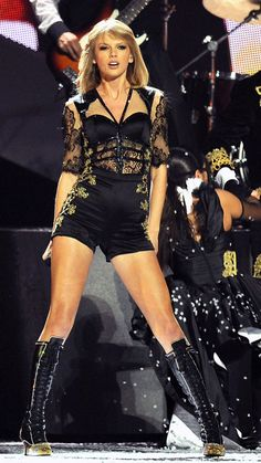 Taylor Swift wearing her black sampo dress and her black wrestling boots.