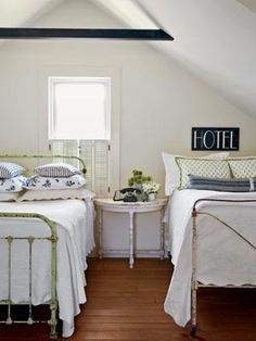 This attic room with twin beds is a perfect hideaway for a guest room. Furniture is kept simple with vintage bed frames and an antique side table. Pillows made from tea towels and a vintage phone and hotel sign add character.  [The idea of using tea towels to cover the pillow opens up more ideas.] ///   guest room at the lake