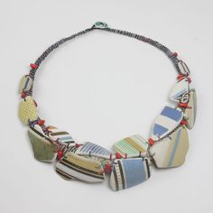"Amanda Caines creates unique hand stitched and bound fabric jewellery and icons using semi precious stones, wood, object d'art and tumbled glass.  ""I love the fact that I am creating contemporary jewellery using discarded pieces that have been worn and loved. I feel it lends to my work a sense of history and continuity."""