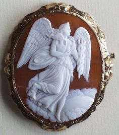 //The Goddess of Healing Cameo    Materials: Shell cameo in a frame of chiselled gold    Date: The cameo was made circa 1820. The frame dates to ca 1880 while the clasp on the back is a 20th century replacement. There is no pendant bale.  Size: 1 15/16 by 1 1/2 inches  Origin: Italy  Condition: Mint. There is no wear to the high points of the carving. There are no chips, cracks or surface flaws. The frame is undented.