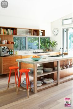 The playful mid-century modern vibe in this kitchen is completed by these orange stools