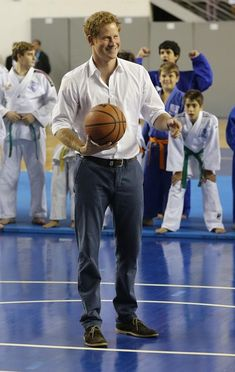 Prince Harry tries his hand at basketball during a visit to Minas Tenis Clube on the second day of his tour of Brazil on June 24, 2014 in Belo Horizonte, Brazil.