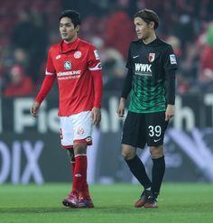 Yoshinori Muto of Mainz chats with Takashi Usami of Augsburg during the Bundesliga match between 1. FSV Mainz 05 and FC Augsburg at Opel Arena on February 10, 2017 in Mainz, Germany.