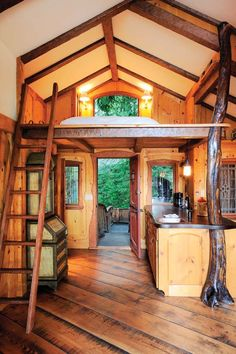 This treehouse's charm is emphasized by personal touches throughout the home. The fir countertop in the kitchen is filled with visitors' names carved into the surface. | Tiny Homes