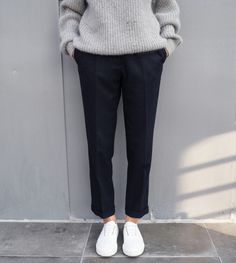 Black trousers paired with slouchy sweater and sneakers