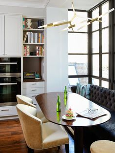 elegant kitchen nook + modern lighting + tufted sofa