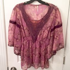 Free People Sheer Lace Peasant Blouse A fun and super flirty semi-sheer blouse by Free People that is sure to flatter even the harshest of critics. Featuring beautiful crochet and lace detailing in a deep v-kneck at the center-front portion of the piece, which mixes sassy shades of purple with ikat printing for an ultra-edgy touch. Flutter batwing sleeves and an elasticized waist complete the look for that oh-so-chic Free People touch. Item is pre-owned but was very well-cared for and is in…