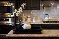 Chris - The white subway tiles brighten up the room and look good with the dark cabinets. The counter top ties both together.