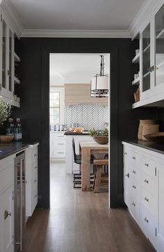 Black and white butler's pantry features walls painted black lined with white cabinets paired with black countertops. Black and white butler's pantry features walls painted black lined with white cabinets paired with black countertops. Kitchen Cabinets Black And White, Backsplash With Dark Cabinets, Black Countertops, Kitchen Pantry Cabinets, Black Kitchens, White Cabinets, Cool Kitchens, Kitchen Backsplash, Black Painted Walls