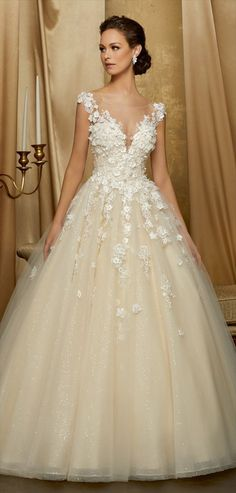 A tulle ball gown with hand-cut, crystal beaded, three dimensional floral appliques and illusion neckline and back.