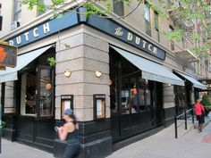 Exterior view of the Dutch, a restaurant on the corner in Soho with light stone facade, big windows and cheery awnings