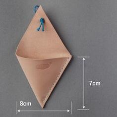 【商品について】その名も▲。三角と呼びます。 1辺が8㎝の正三角形のコインケースです。切りっぱなしなので、コバ(革の断面)は磨いておりません。つくりはいたってシンプルに素っ気なく。ブルーの紐で蓋をするだけ。たくさんのコインは入りませんがちょっとしたお買いものなら特に問題ないサイズです。【つくりについて】使用している革はフランス産原皮をイタリアで鞣した昔ながらの100%植物タンニンなめしです。ヌメ革は、最初は多少硬くてそっけない牛革になりますが、使用すると徐々に革が本来持っている脂分や手の脂、日光によって変化する大変味わい深い素材になります。自分のつかい方で革を育てる楽しさがあります。手縫いはミシン縫いよりも時間が多くかかりますが、温かみと強度を兼ね備えた手縫いにこだわっています。本商品は糸がほつれた場合無償で修理いたします。