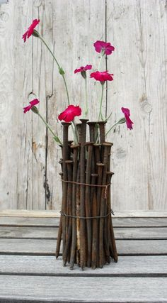 A basic flower pot surrounded and tied together by stick branches. This just adds more flamboyant coloring to the flowers<3