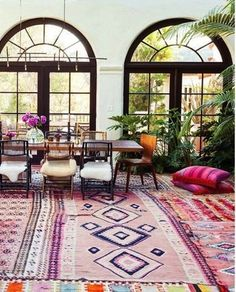 Mix up your dining chairs and layer your rugs for an eclectic Boho look! Love this indoor/outdoor dining area.