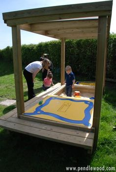 Raised sandbox w/ pergola-type roof, bench seating, and flip-over cover that can also be used as play area.