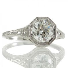 A platinum Art Deco solitaire ring featuring a 1.05ct transition cut diamond grain set within an octagonal bezel style mount with a double row of millegraining to the edges surmounting a pierced floriate gallery which flares out to join the engraved and pierced shoulders all tapering down to a plain polished band. #RutherfordJewellery #Melbourne