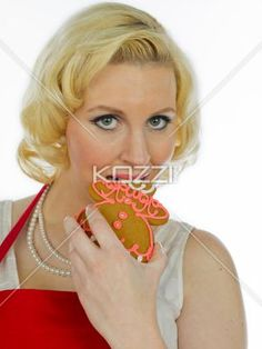 close-up of a young woman eating a gingerbread man. - Close-up portrait of a young woman eating a gingerbread man against white background.