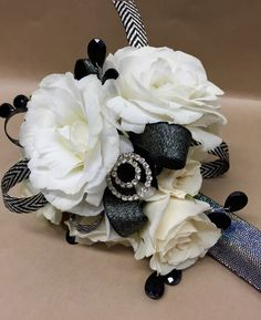 wrist corsage featuring white lisianthus and white tea roses with accents of black ribbon, black gems and rhinestones – shown on black snap bracelet - $44.95 #prom #promflowers #leighflorist