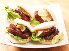 pork-belly-bun-recipe 1/2 cup soy sauce 1/2 cup mirin 1/2 cup granulated sugar 2 tablespoons fish sauce 2 whole scallions, roughly chopped 3 medium cloves garlic, roughly chopped 1 (2-inch) chunk ginger, peeled and roughly chopped 2 1/2 pounds pork belly,  1 or 2 whole slabs 2/3 cup mayonnaise,  homemade 24 fresh or frozen Chinese-style steamed buns 1 head bibb lettuce, washed, dried, and torn into medium-sized pieces 1 recipe Quick-Pickled Cucumbers with Rice Vinegar