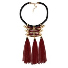 The Janet tassel bib necklace is a standout bib. A geometric formed collar necklace accented with metal tubes, twisted rope, beads and chains makes this tassel bib necklace a statement piece. construc