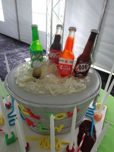 """""""Soda Bottle Bucket"""" Mitzvah cake. The ice is smashed sugar, the bucket is fondant on buttercream and cake, and the bottles are cast from colored isomalt sugar."""