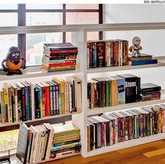 No andar de cima do dúplex, em vez de guarda-corpo há uma estante de madeira. Além de acomodar os livros, permite a passagem da luz natural. Projeto do escritório Marques Kalaidjian Arquitetura.